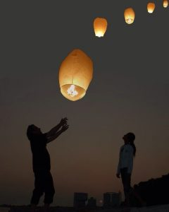 couple releasing lanterns in the night sky